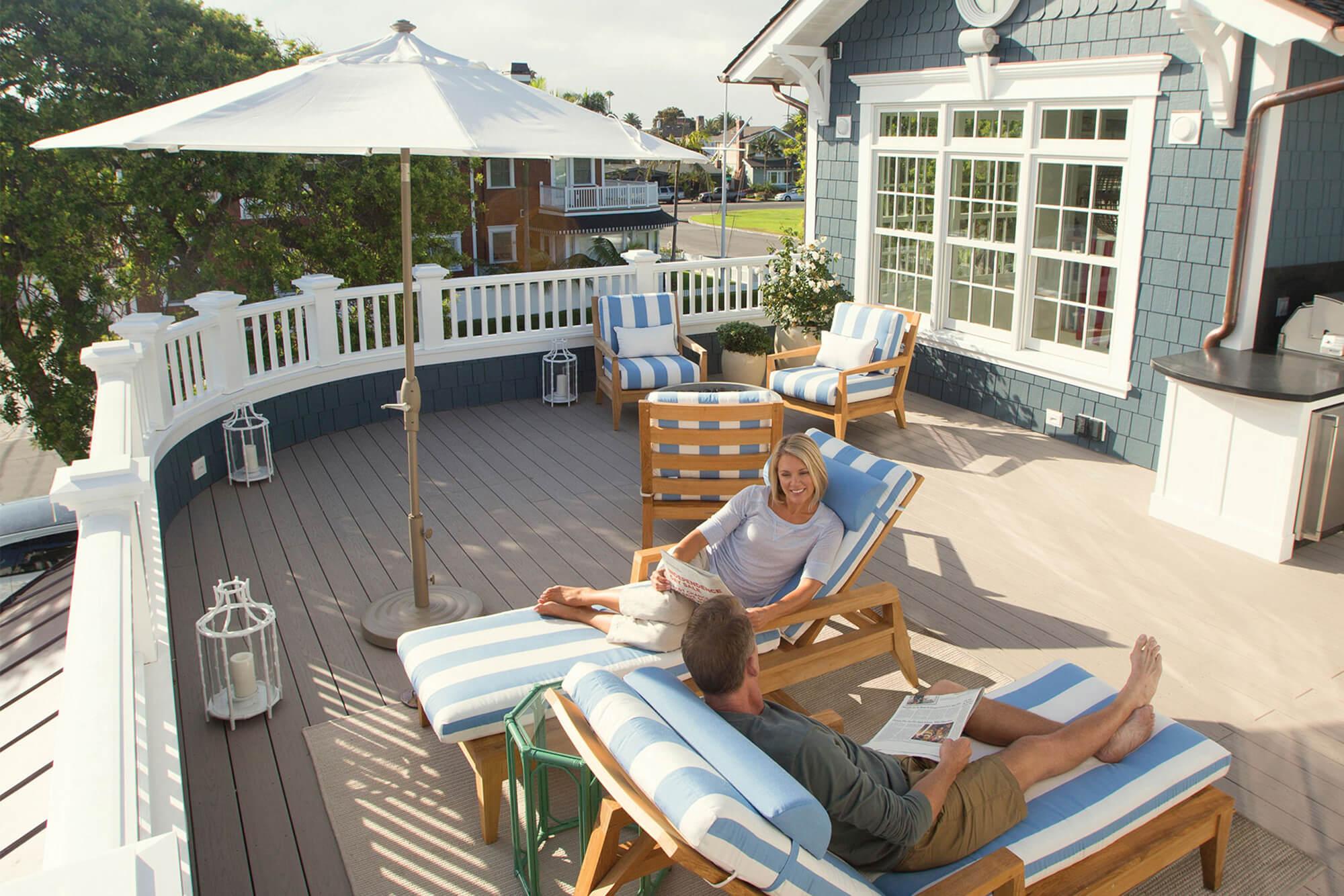 마당에 설치된 양산 아래의 실외용 가구에서 휴식을 취하고 있는 커플