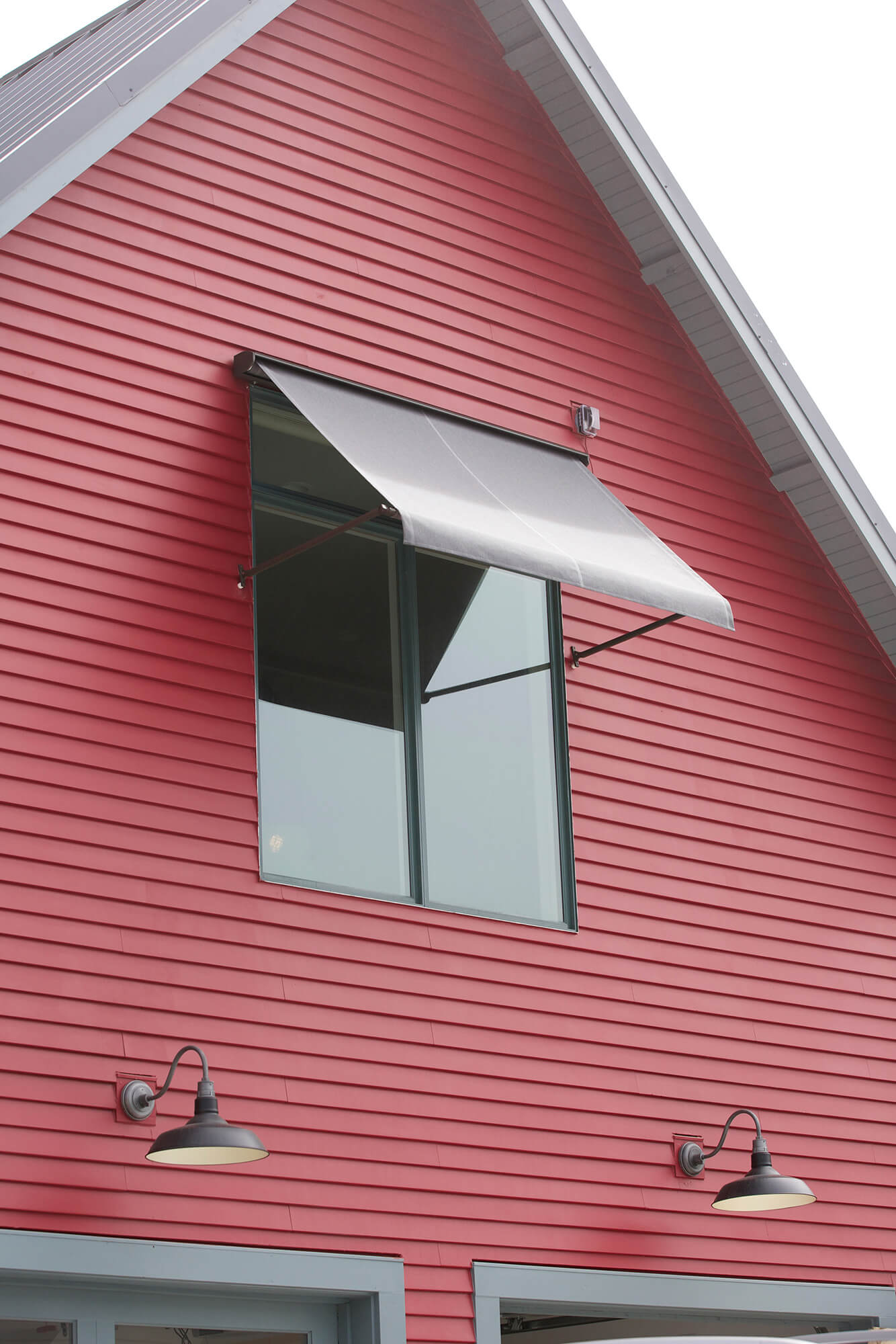 Red house with window awning made using grey Sunbrella fabric