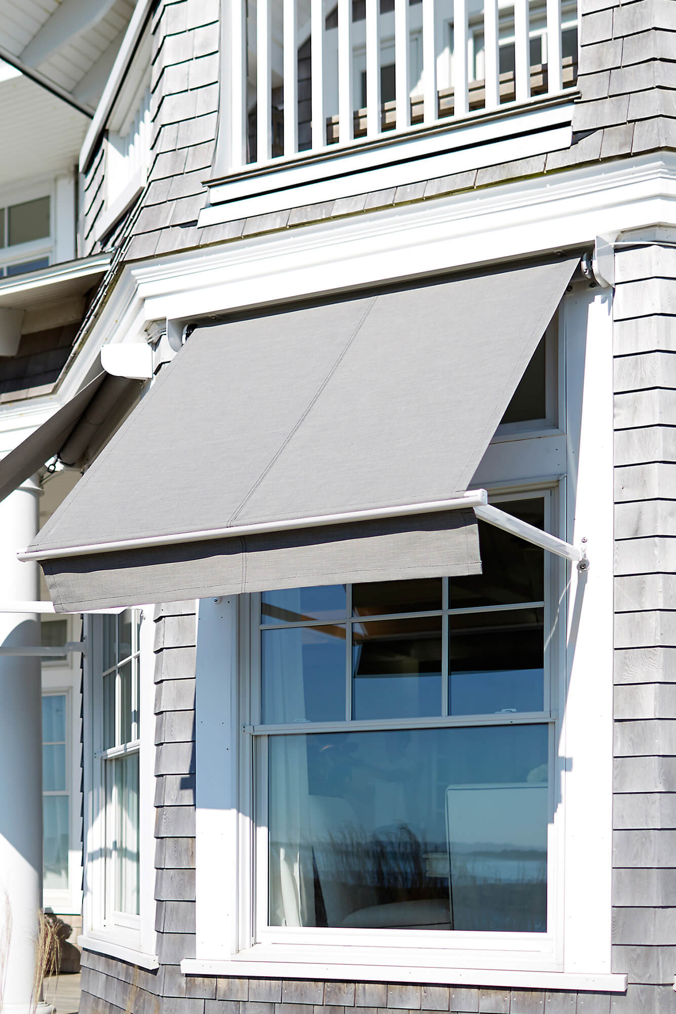 A home with many windows features multiple window awnings with grey Sunbrella fabric