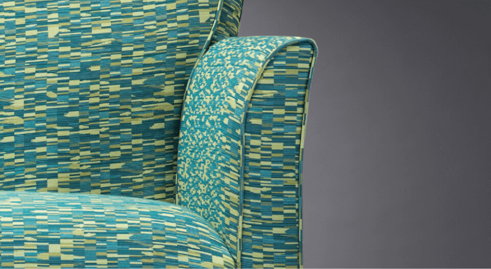 Close up detail of a teal patterned chair covered in Sunbrella Contract fabrics