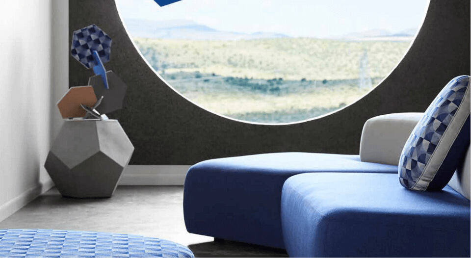 A blue sofa with white back and a colorfully coordinated mobile sits in the background by the window