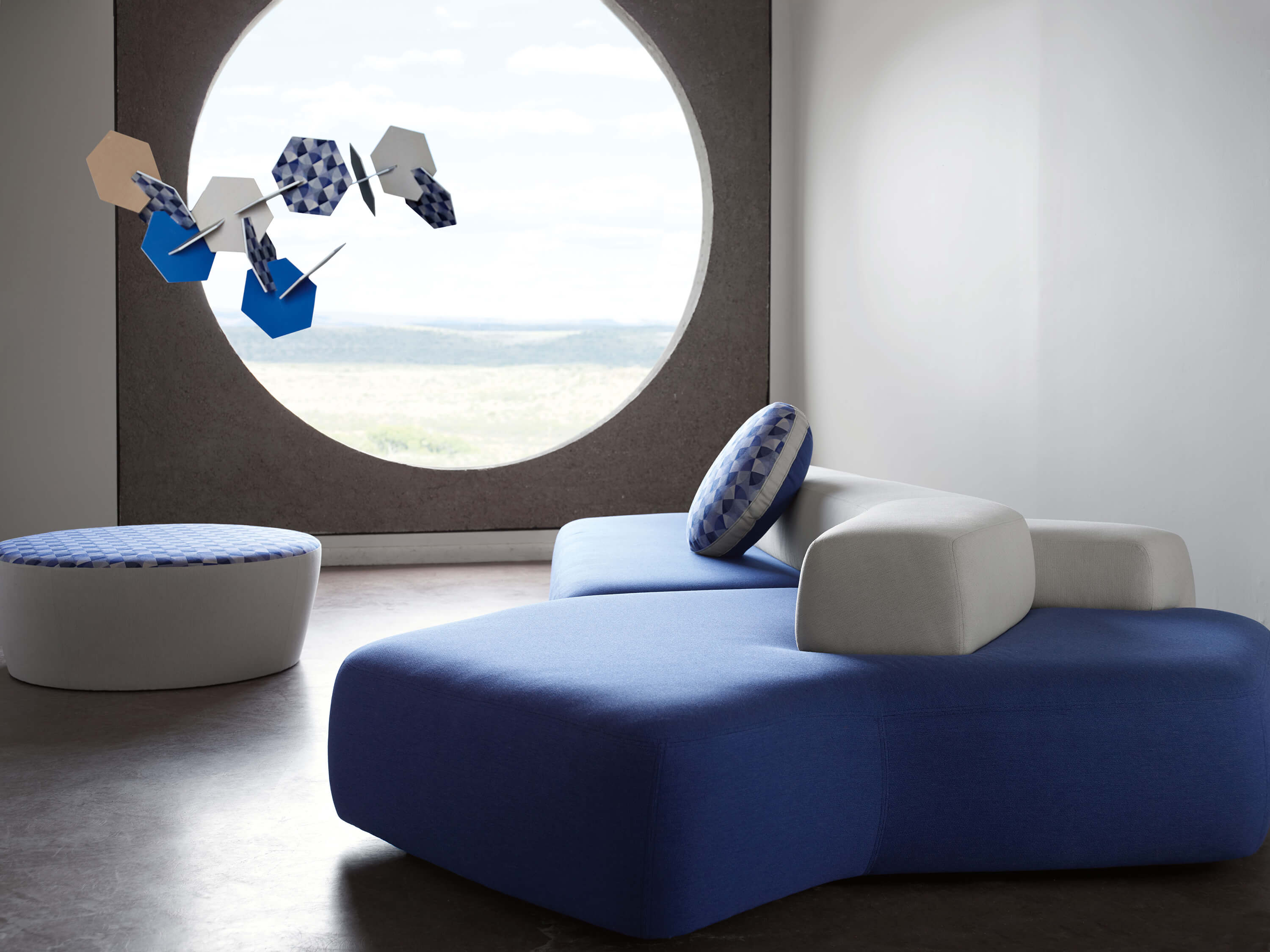 A Sofa Upholstered In Blue Sunbrella Contract Fabrics Sits In A Waiting Room