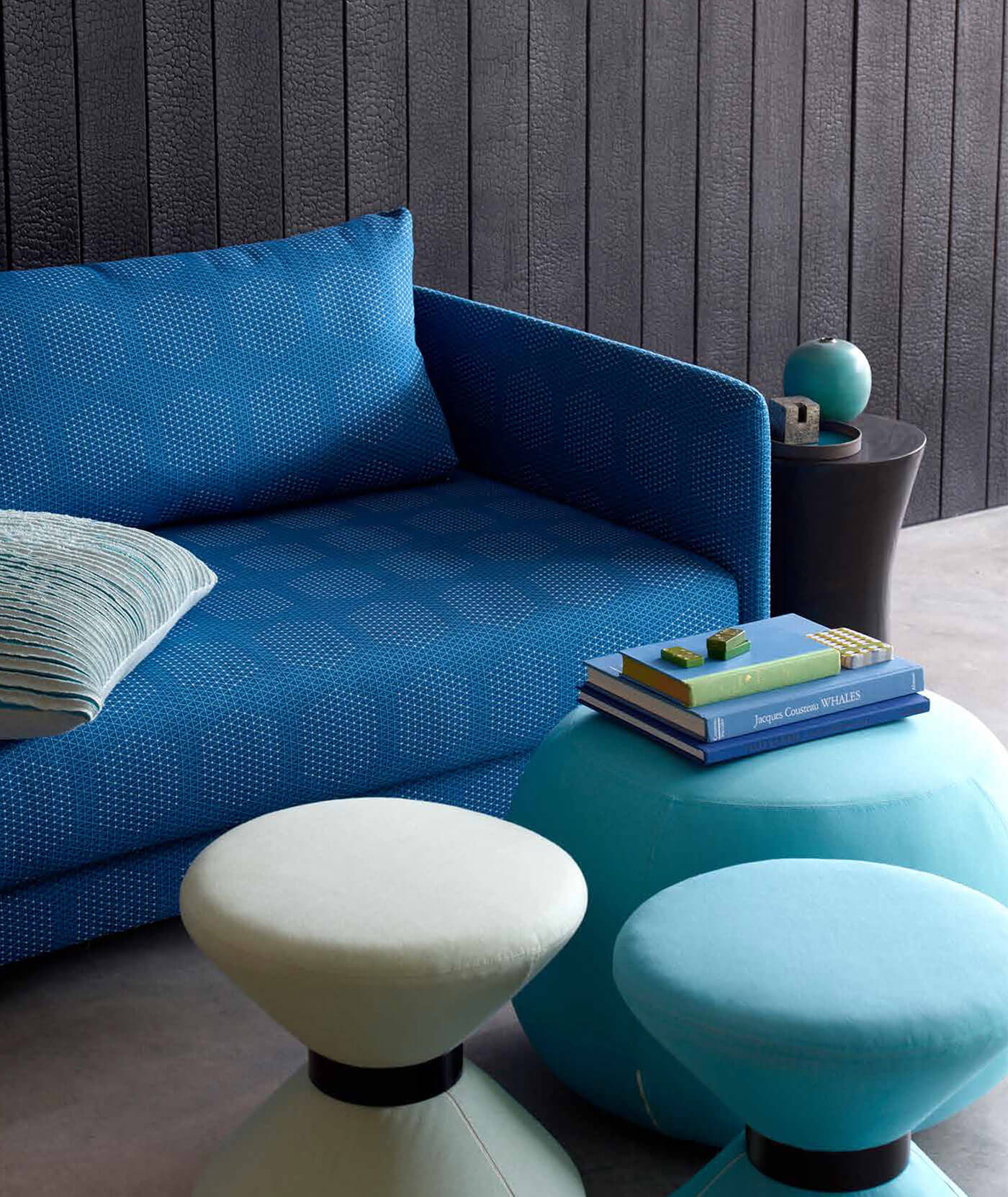 A blue sofa covered in Dot Structure Sunbrella Contract fabric with coordinating teal and white pouffs