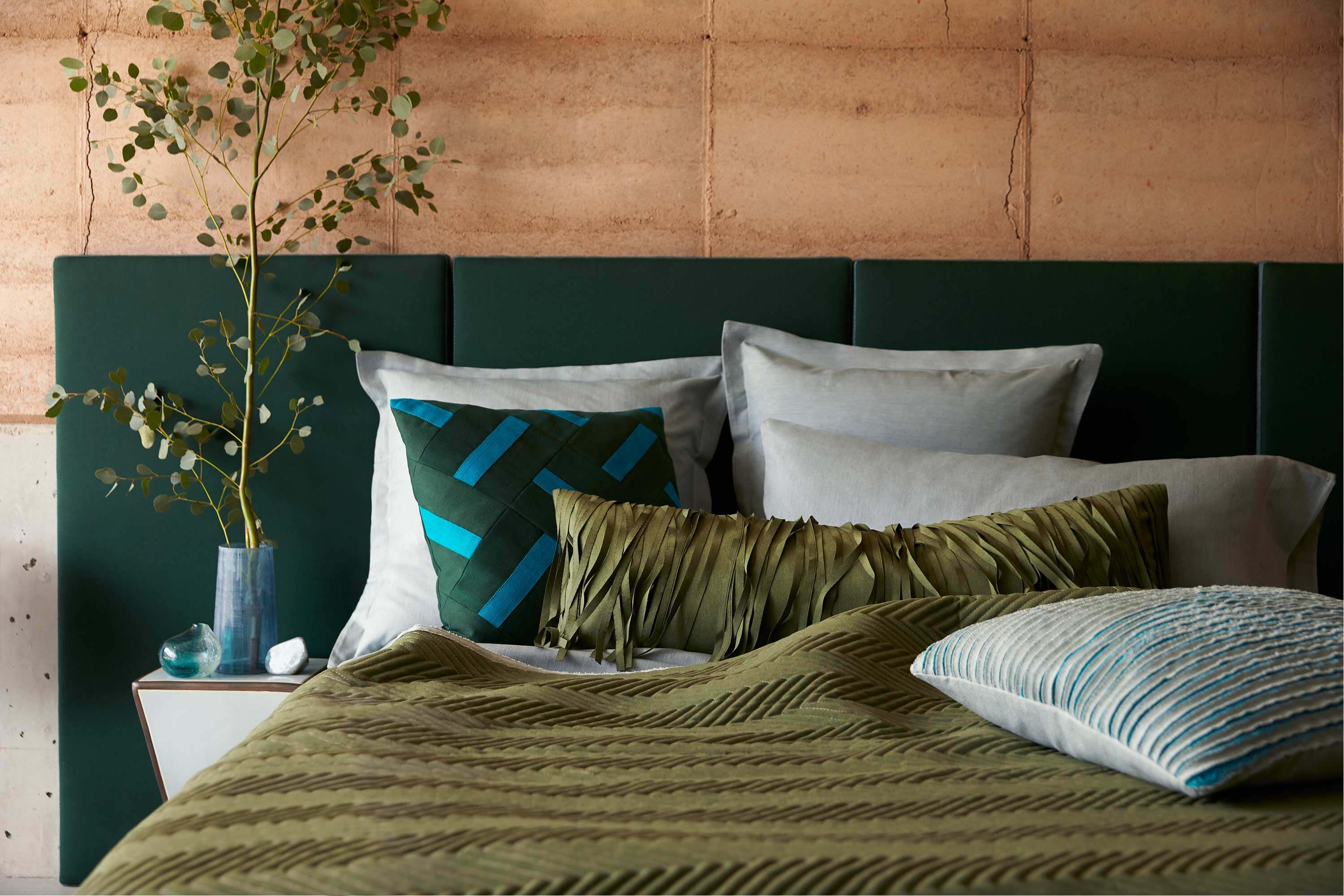 Bedroom with headboard, plillows and coverlet made with green and teal Sunbrella fabrics