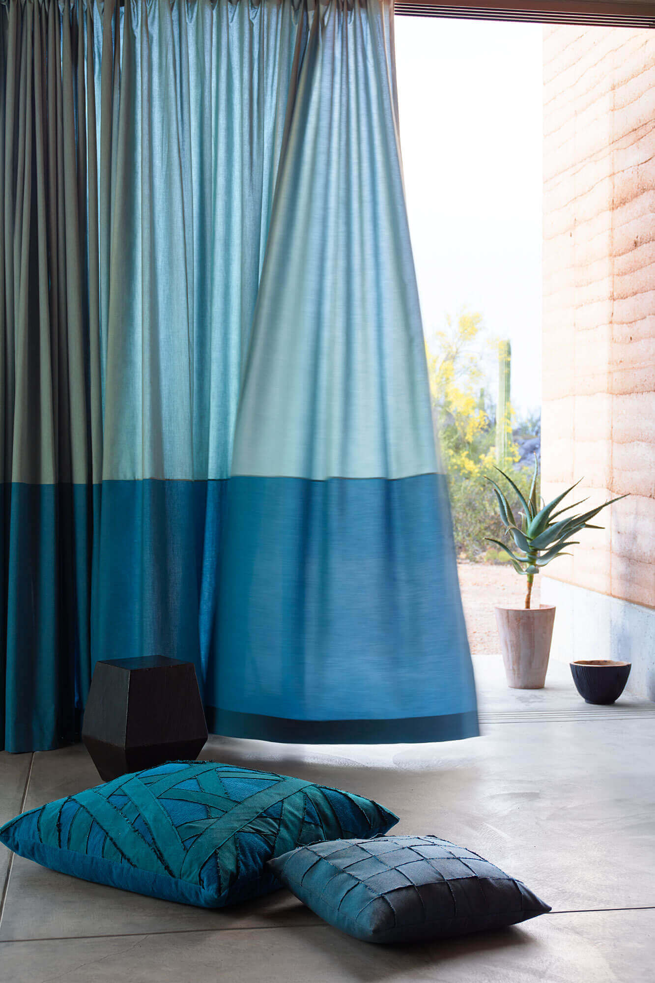 blue drapery flows in the wind with decorative pillows on the floor - Sunbrella Pillows