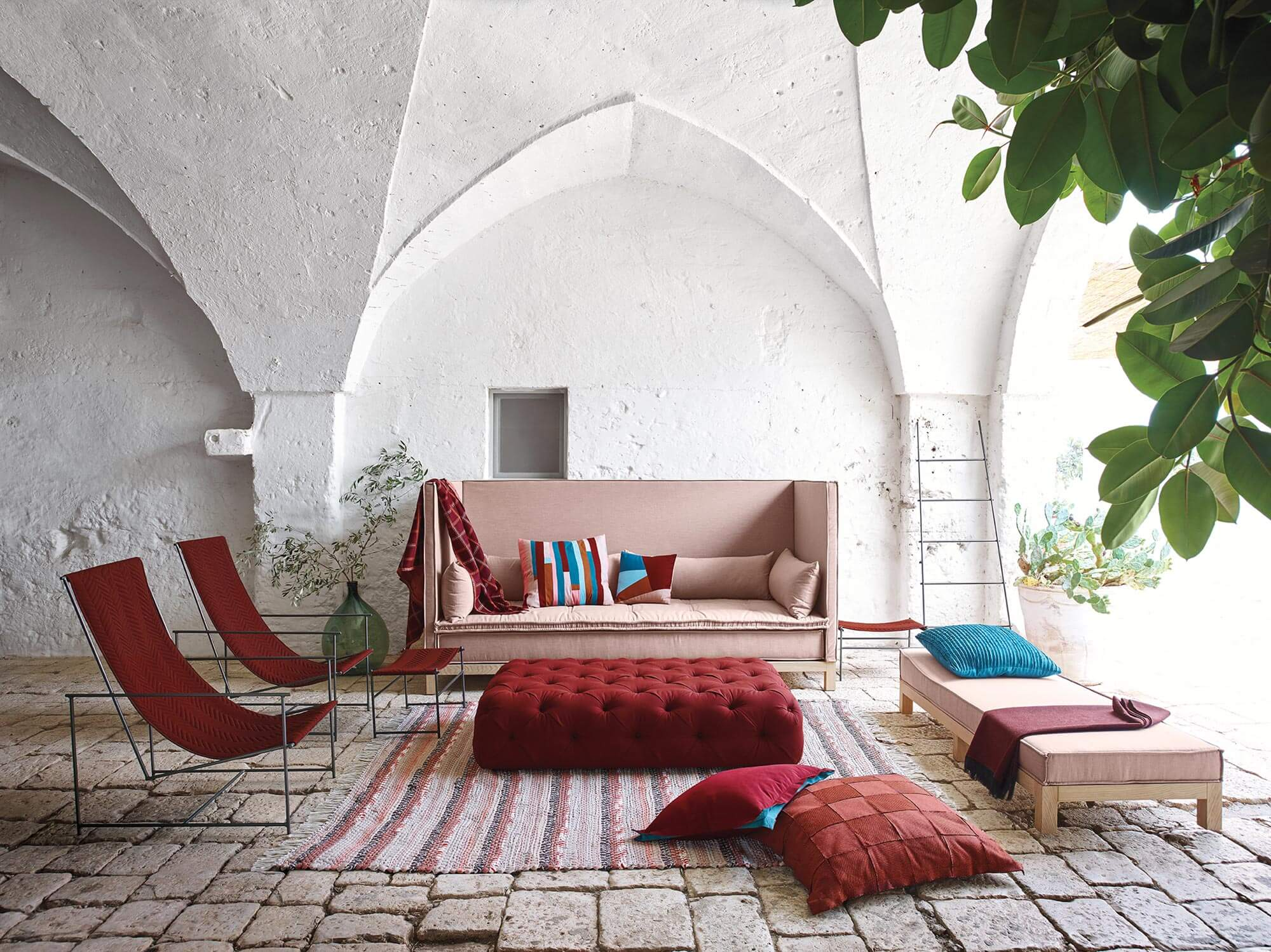 A living room with a large sofa, chairs, and a tufted ottoman in hues of red and pink are made using Sunbrella upholstery fabric.