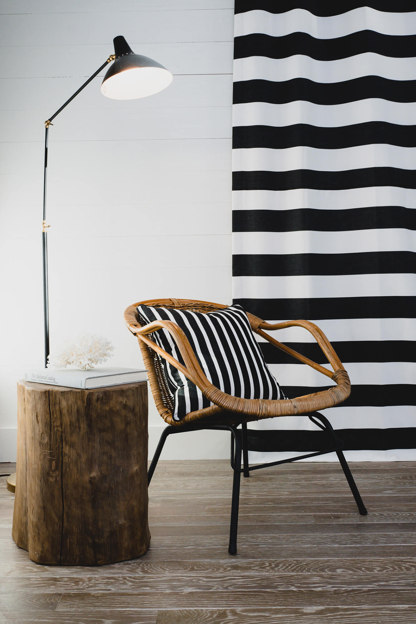 Living room chair with throw pillow featuring black and white striped Sunbrella fabric and black and white striped drapery in background