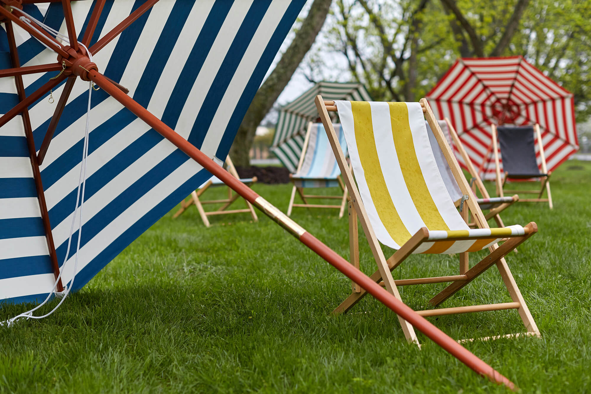 Outdoor chairs and market umbrellas featuring bright cabana striped fabric