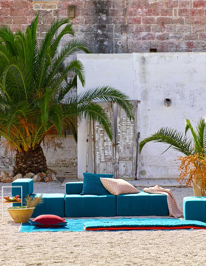 Teal seating cushions with palm trees and brick wall background.