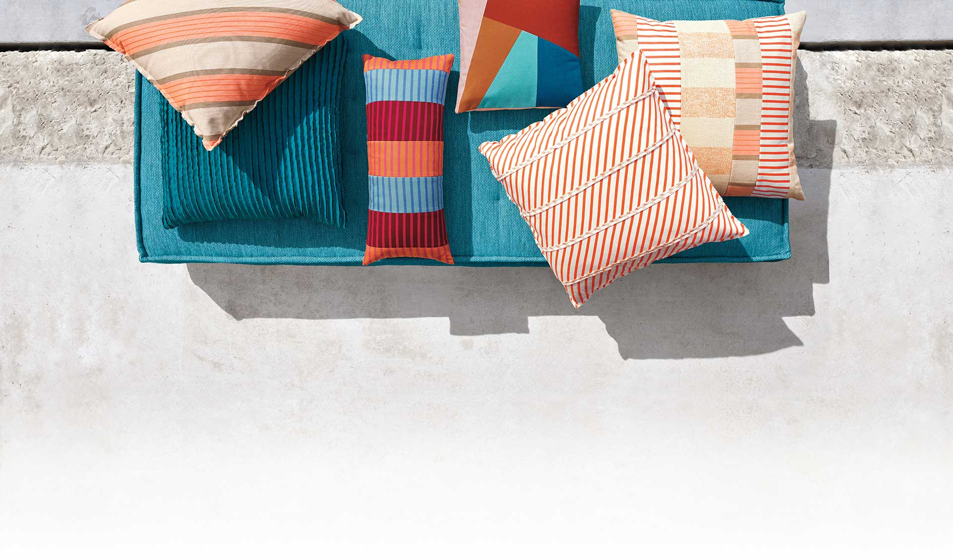 Close-up photo with teal floor cushion with pillows.