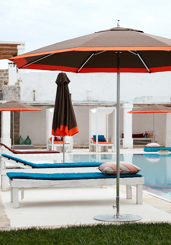Brown umbrellas with orange trim, lounge seating, poolside.
